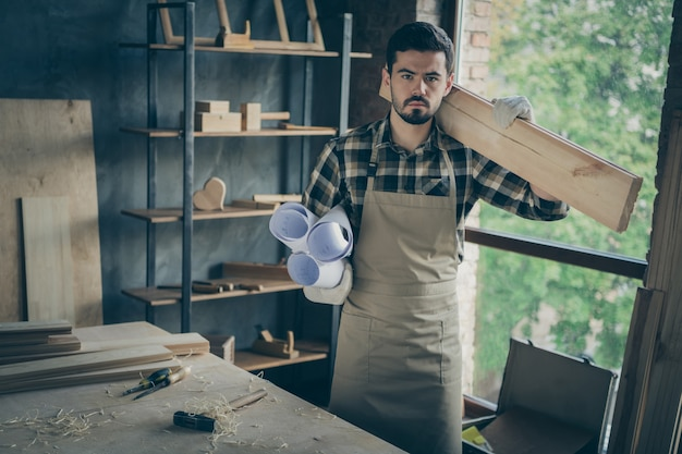 Serious confident man holding wooden block on his shoulder and rolls of blueprints with the other hand standing near desktop with filings on