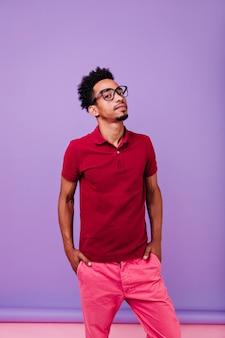 분홍색 바지 포즈에 심각한 자신감 남자입니다. 검은 곱슬 머리를 가진 잘 생긴 남자의 실내 샷.