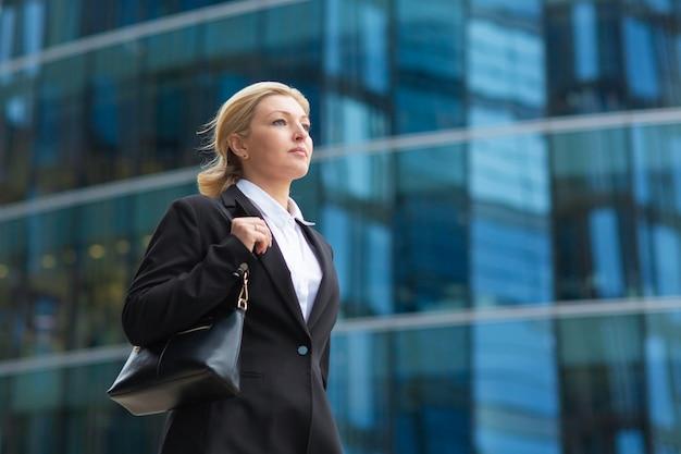 深刻な自信を持って中年女性のオフィススーツを着て、バッグを保持し、ガラスのオフィスビルを過ぎて歩いています。ローアングル、コピースペース。都市のコンセプトの女性実業家