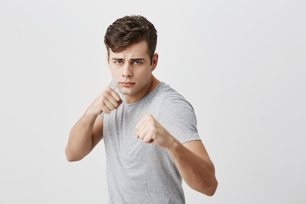 Serious confident muscular young sportsman frowns face in displeasure, shows clenched fists, demonstrates strength and irritation, ready to defend himself. power and strenght concept.