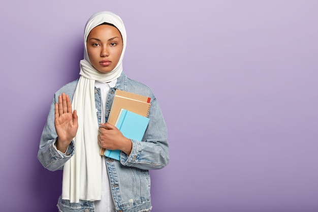 Serious confident muslim woman holds notepads, shows palm as sign of refusal or rejection, wears white scarf and denim coat, asks to wait minute, poses over purple wall, blank space