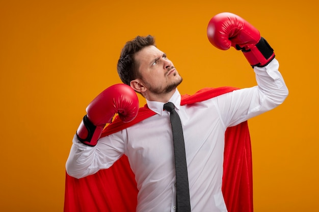 Serious confident super hero businessman in red cape and in boxing gloves raising hands showing strength and courage standing over orange background