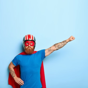 Serious confident superhero pretends to fly, wears red cape, mask, protective helmet