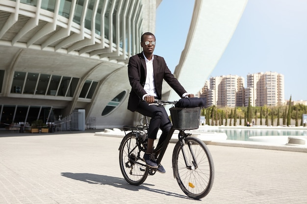 Serious and confident young african american male office worker wearing mirrored lens shades and formal black suit cycling