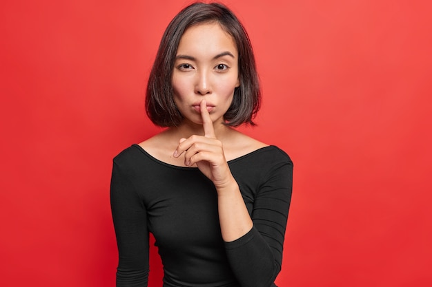 Serious confident young asian woman makes silence gesture keeps index finger over lips tells secret or confidential information wears black long sleeved dress isolated over bright red wall.