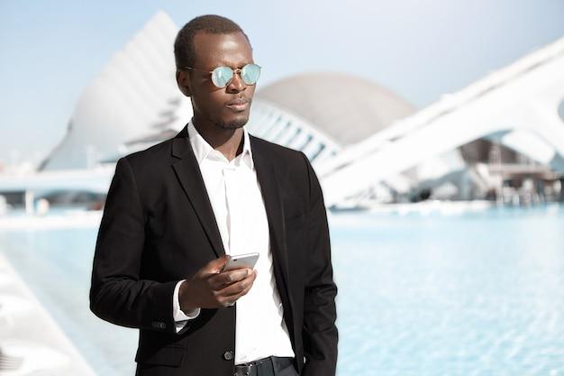 夏の晴れた日に屋外でスマートフォンを使用して深刻な自信を持って若いビジネスマン