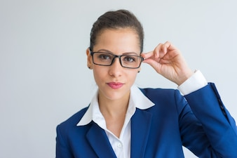 Serious confident young businesswoman adjusting eyeglasses and looking at camera.