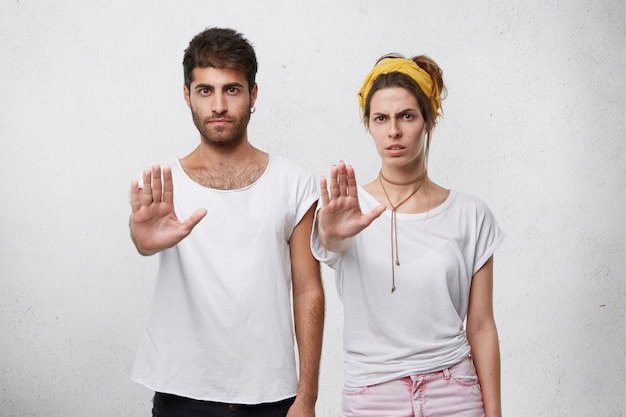 Serious confident young male and female both making stop gesture with outstretched arms, showing their disagreement or protest