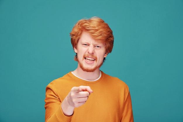 질문할 때 당신을 가리키는 수염을 가진 진지하고 자신감 있는 젊은 빨간 머리 남자