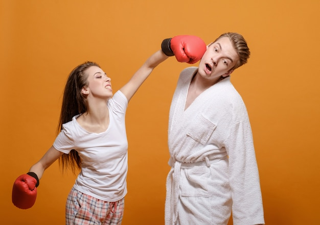 Serious conflict between man and woman, woman in boxing gloves, woman beats a man, domestic violence