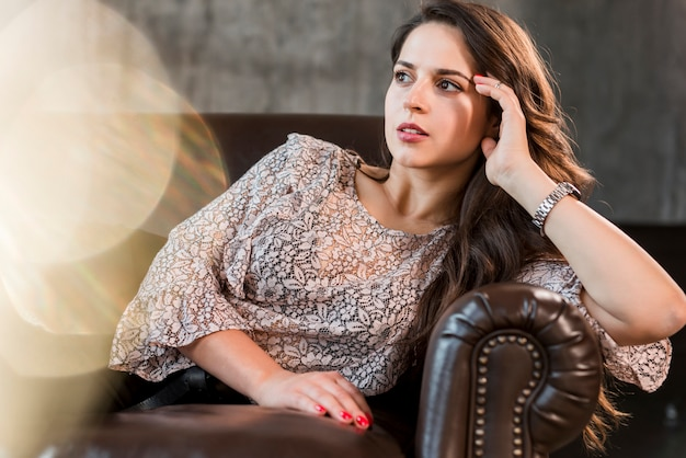 Serious contemplated young woman leaning on brown sofa