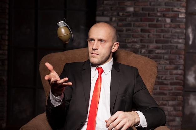 スーツと赤いネクタイを着た深刻な契約殺人犯が冗談めかして手榴弾を投げます。