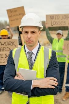 Серьезный подрядчик противостоит толпе недовольных строителей с плакатами