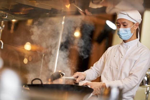 Серьезный повар готовит горячую еду на кухне
