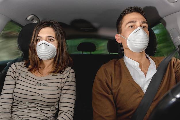 얼굴 마스크를 쓰고 차 안에서 심각한 부부. 건강 보호, 안전 및 유행병 개념. 코로나 바이러스 대유행 중 운전.