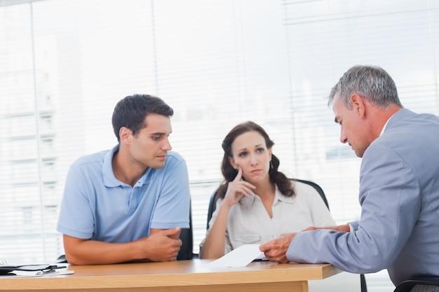 Серьезная пара, беседующая с агентом по недвижимости