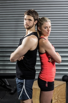 Serious couple standing back to back at crossfit gym