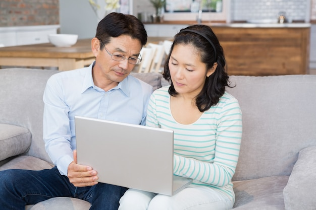 Serious couple using laptop on the sofa
