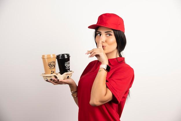 Серьезный курьер делает знак тишины с двумя чашками кофе. фото высокого качества