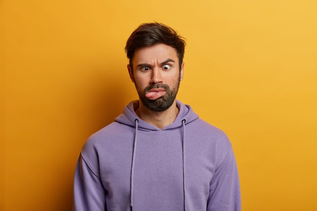 Serious crazy bearded man crosses eyes and sticks out tongue, has funny grimace, feels bored, raises eyebrows, wears casual hoodie, isolated on yellow wall. human face expressions concept
