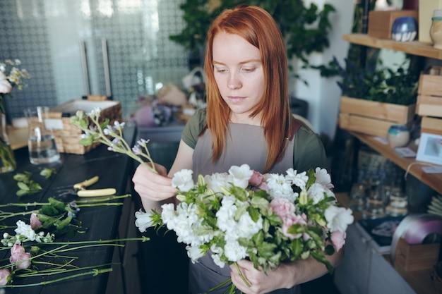 Серьезный креативный рыжий флорист в фартуке, стоящий за столом с инструментами и цветами и составляющий свадебный букет в собственной мастерской