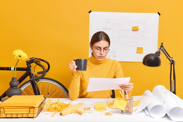 Serious creative woman makes sketches at desktop poses at desk concentrated into paper drinks coffee poses in cozy office surrounded with blueprints