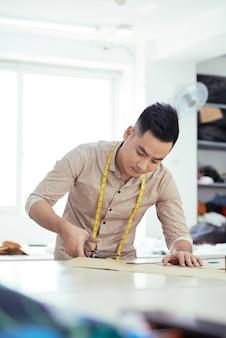 彼がワークショップで作っている新しいスーツのために生地を切る真面目な創造的な若い男