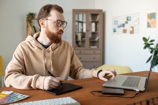 ホームオフィスで描画パッドを使用してデザインプロジェクトに取り組んでいるパーカーの真面目な創造的な若い男