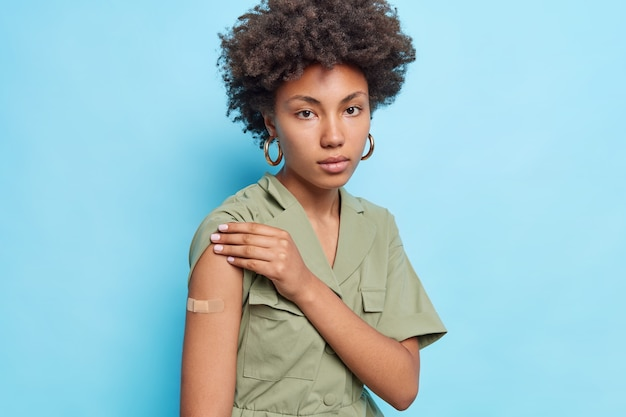 Serious curly afro american woman shows plastered arm got second dose of vaccine wears dress looks directly at front isolated over blue wall