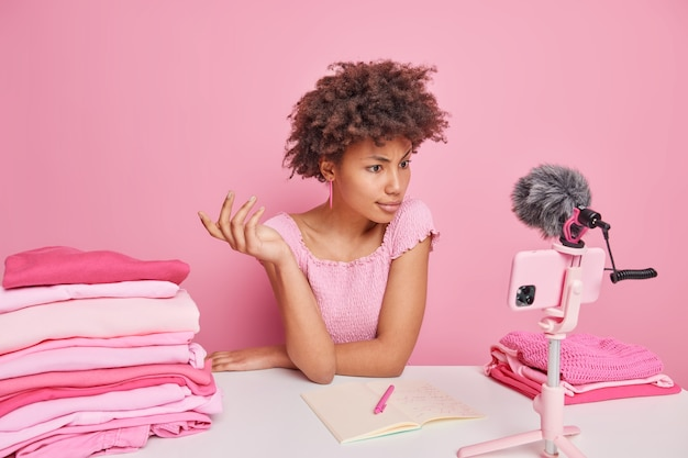Serious curly afro american woman watches tutorial video via smartphone makes notes how to do laundry writes down washing temperature of different clothes items sits at table against pink wall