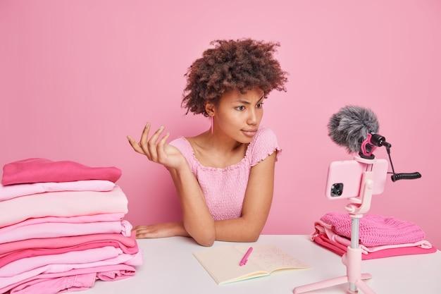 곱슬곱슬한 아프리카계 미국인 여성은 스마트폰을 통해 튜토리얼 비디오를 시청하고 분홍색 벽에 기대어 테이블에 앉아 다양한 옷의 세탁 온도를 기록하는 방법을 기록합니다.