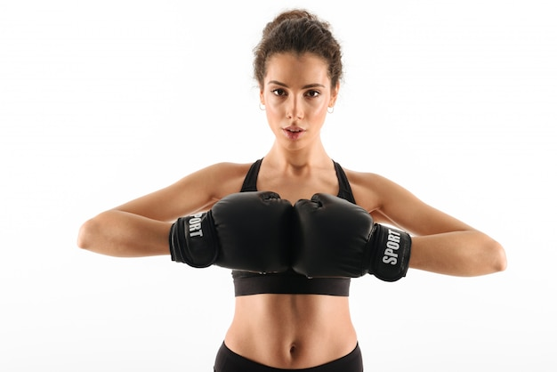 Serious curly brunette fitness woman in boxing gloves