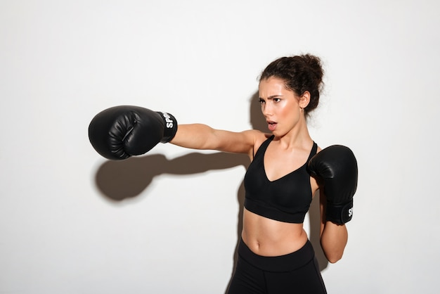 Serious curly brunette fitness woman trains in boxing gloves