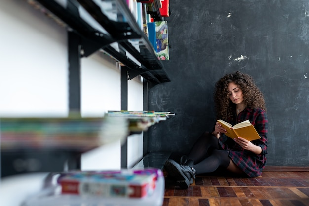 Serious curly brunette girl reading a book in her hand