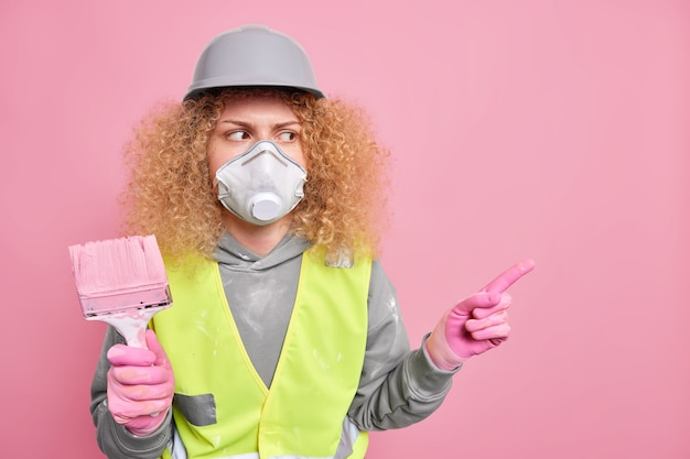 Serious curly haired female painter wears protective helmet respirator and gloves holds painting brush dressed in workwear points away on blank space on pink