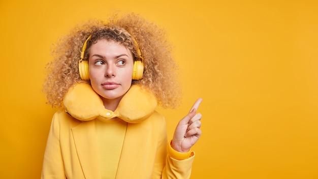 Серьезная кудрявая модель миллениала дает рекомендации, указывает на пустое место для копирования, носит стереонаушники на ушах, дорожная подушка вокруг шеи, изолированная на желтой стене