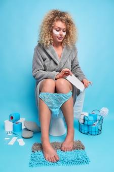 진지한 곱슬머리 여성은 화장지를 사용하여 눈 밑에 패치를 적용하고 목욕 가운을 입은 화장실에서 파란색 벽에 격리된 카펫에 발을 유지합니다