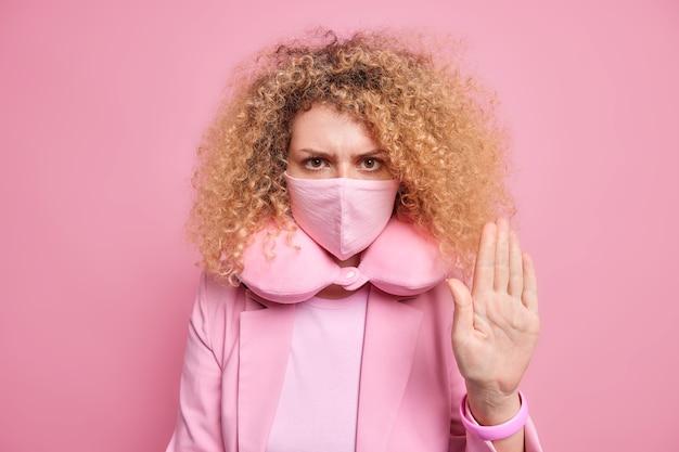 Серьезная кудрявая женщина просит не забывать о маске, требует жестов стоп, чтобы сохранить социальную дистанцию, использует защитные средства во время вспышки пандемии коронавируса, носит подушку для шеи