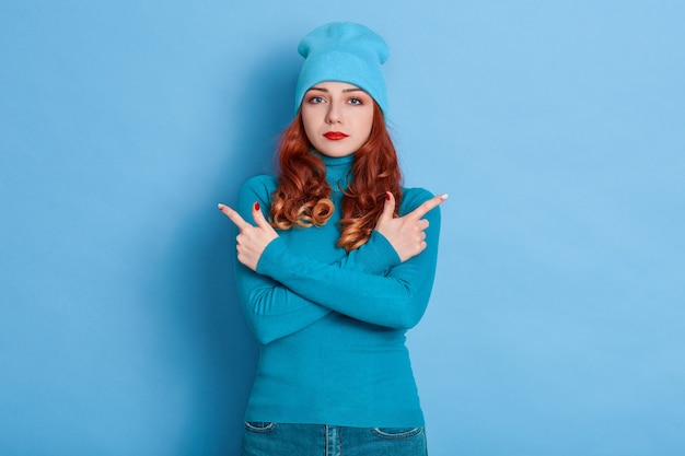 Serious curly haired woman crosses arms over chest, points left and right, wearing jumper and cap