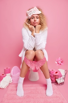 임신 테스트 결과를 기다리는 진지한 곱슬머리 여성은 잠옷을 입고 변기에 목욕 가운을 입고 엄마가 될 앞을 직접 본다