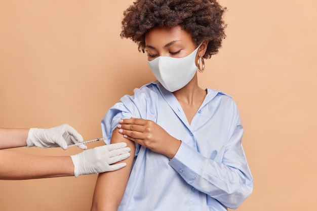 Serious curly haired woman wears protective face mask against virus wears blue shirt receieves inoculation in shoulder isolated on beige wall
