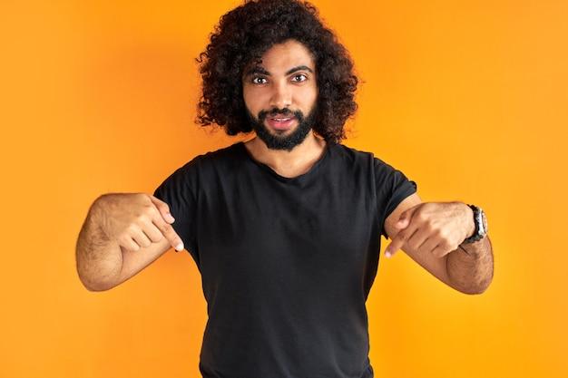 カジュアルな服を着た人差し指で真面目な呪いの男が下を向いて、広告コンテンツのための空きスペースを示しています