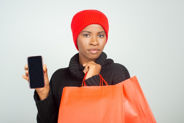 Serious customer in winter sweater and hat holding shopping bags