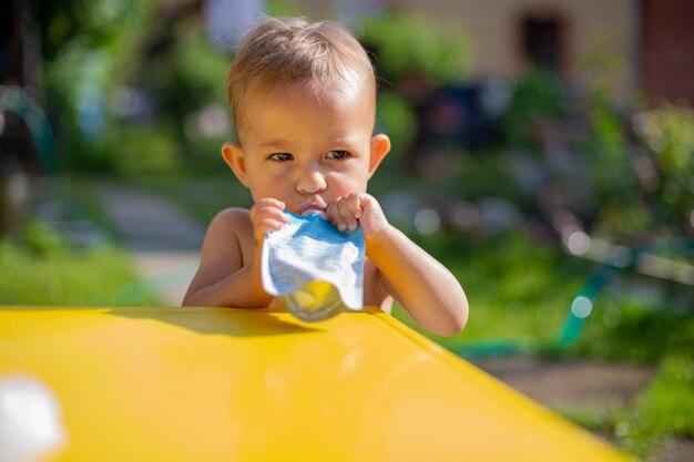Серьезная милая девочка ест фруктовое пюре в сумке и смотрит в камеру перед желтым столом. на заднем плане зеленый сад в солнечный день в размытом