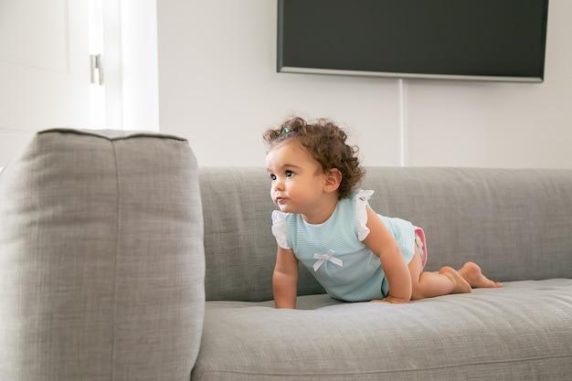 심각한 귀여운 어두운 곱슬 머리 아기 소녀 창백한 파란색 천을 입고 집에서 소파에 크롤 링, 멀리 찾고. 가정 및 어린 시절 개념에서 아이