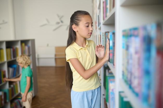 심각한 검은 머리 백인 소녀와 공공 도서관 책장 앞에 서 있는 금발 소년