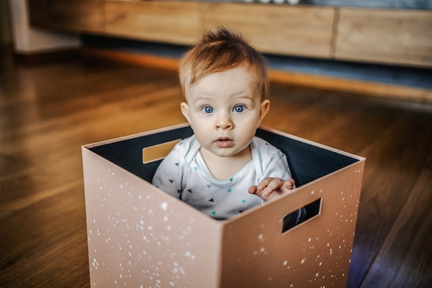 Serious cute little blond boy sitting in box with his big blue eyes. home interior.