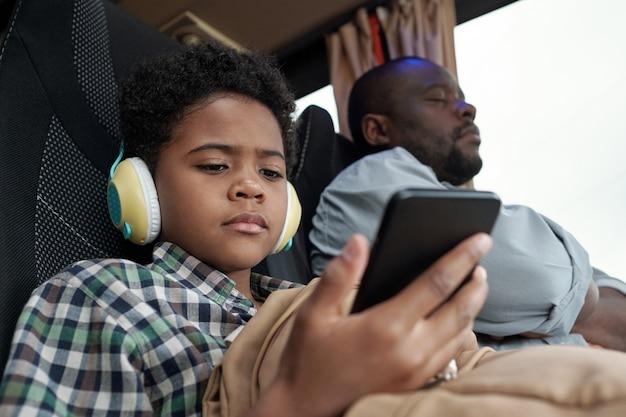 Серьезный милый маленький мальчик, глядя на экран смартфона