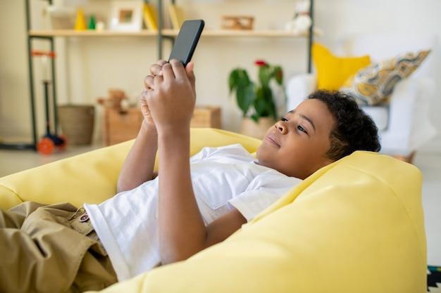 カメラの前のリビングルームでテーブルのそばに座って、のんびりとビデオゲームをプレイするジョイスティックを持つ深刻なかわいい混血の少年