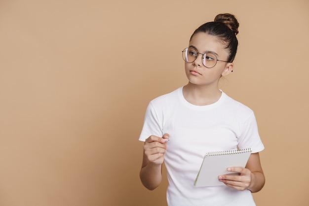 Серьезная, милая девочка-подросток в очках держит в руках блокнот, на чем-то сосредоточившись. милая девушка на коричневом фоне